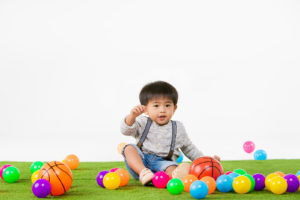 Studio portrait of adorable, Asian toddler boy wearing denim overalls, long sleeve T-shirt, Look at his hands, sit on artificial green grass with multicolored ball, on isolated white background